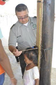 Ein Polizist, der die Ärzte begleitet, misst die Körpergröße eines Wayúu-Mädchens